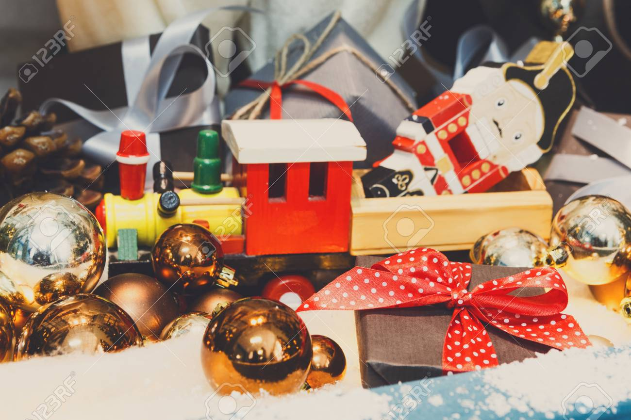 Christmas gifts background. Vintage wooden toy train and nutcracker on snow with golden shiny baubles & Christmas Gifts Background. Vintage Wooden Toy Train And Nutcracker ...