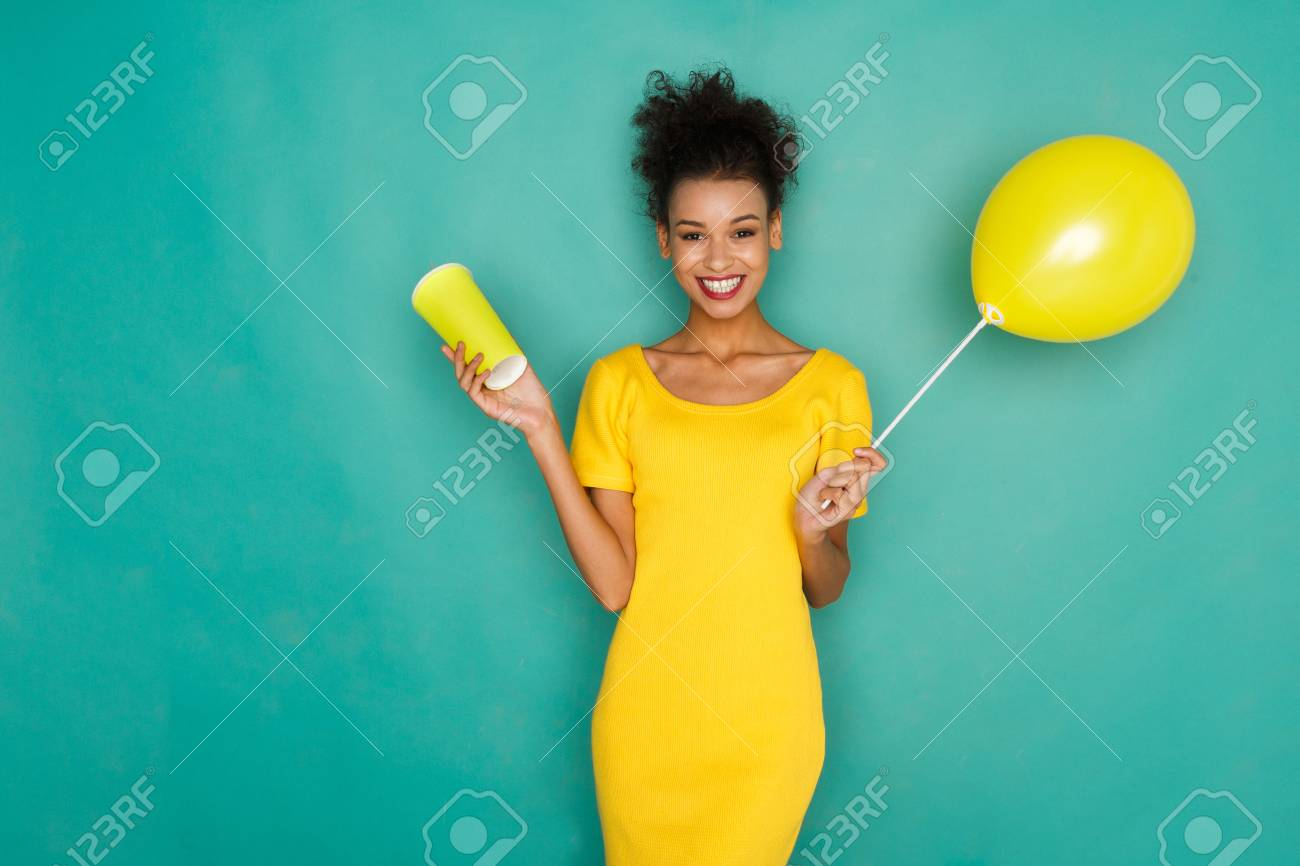a4e44252c782 Smiling curly mulatto girl in bright yellow dress with take away coffee cup  and balloon.