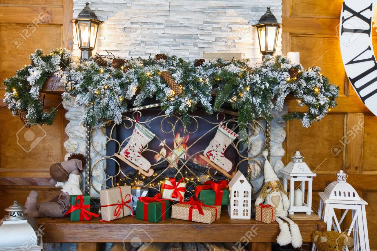 Kamin Mit Tannenbaumkranz Und Girlande Dekoriert. Viele Geschenke Und  Weihnachtsstrümpfe Unter Dem
