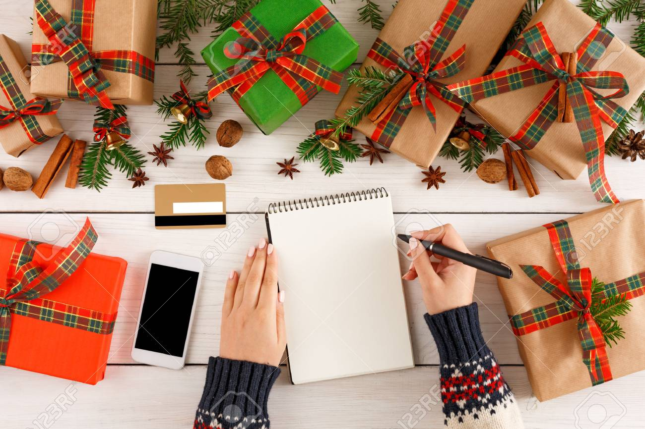 christmas wish list and online shopping background female hands