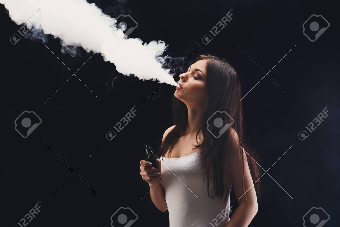cced5df01eb58 Foto de archivo - Mujer morena vaping cigarrillo electrónico con humo sobre  fondo negro. Mujer joven fumando cigarrillo electrónico para dejar el tabaco .