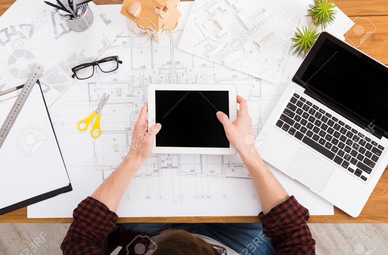 Architect drawing on architectural project on digital tablet architect drawing on architectural project on digital tablet top view on unrecognizable designer hands working malvernweather Gallery
