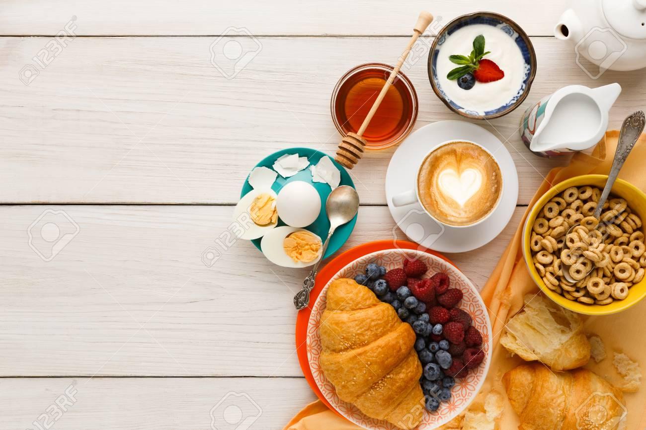 rich breakfast menu background. french crusty croissants, muesli