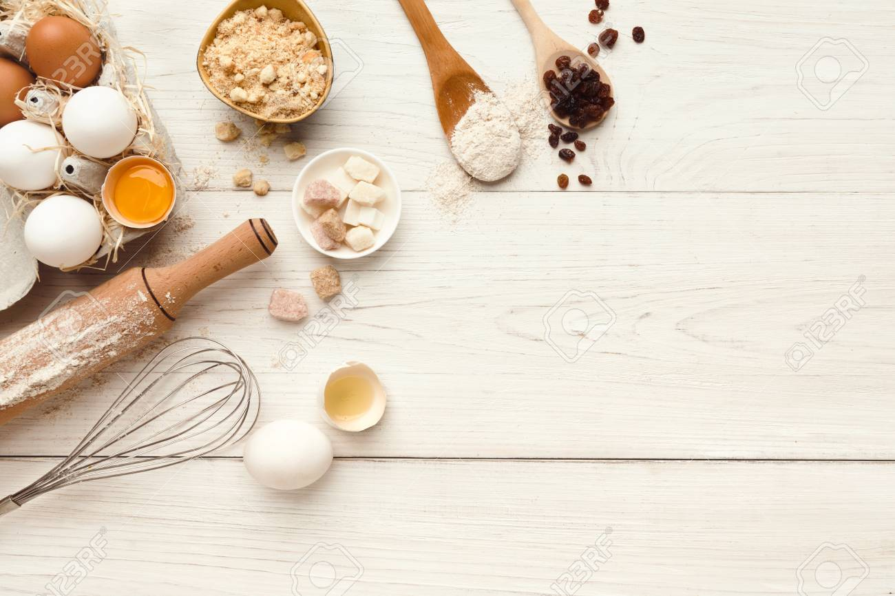 Cooking ingredients background. Border of flour, eggs, raisins, sugar and kitchen utensils on white rustic wood with copy space. Dough preparing and pastry concept, top view - 91033275