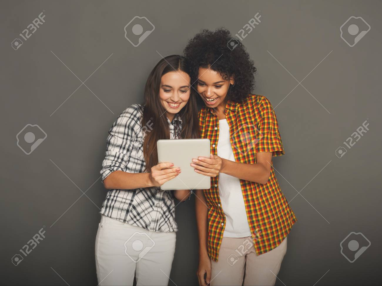 Two happy female friends using digital tablet  Laughing women