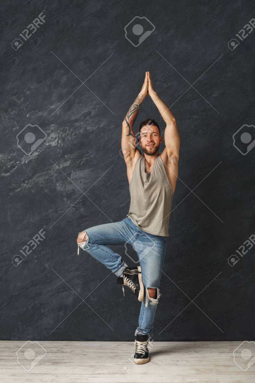 Happy Handsome Smiling Man With Tattoos Making A Yoga Pose Stock Photo Picture And Royalty Free Image Image 94038463