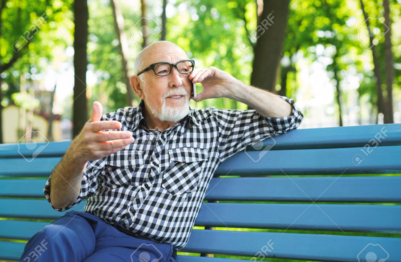 89768f4d4d3c8 Smiling senior man with smartphone outdoors. Elderly casual man in  eyeglasses having emotional conversation on