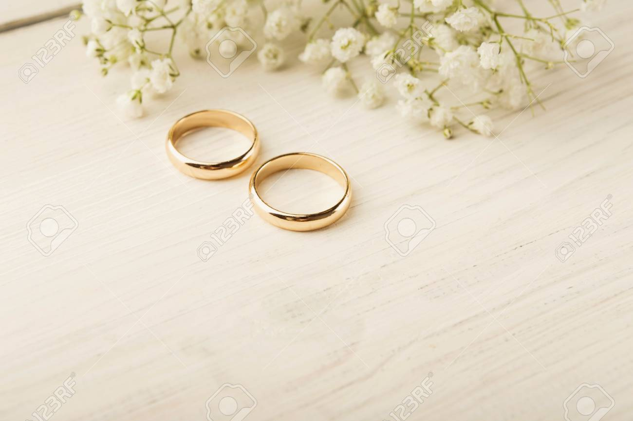 Two Golden Wedding Rings With White Flower Decorations Copy Stock