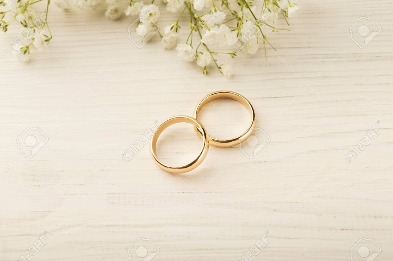 Two Golden Wedding Rings With White Flower Decorations Copy