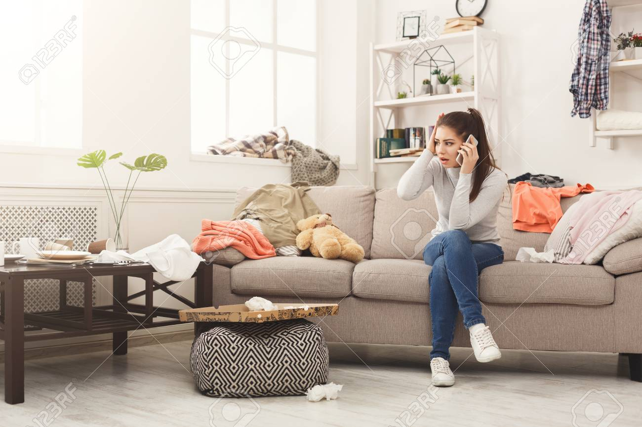 Desperate helpless woman sitting on sofa in messy living room...