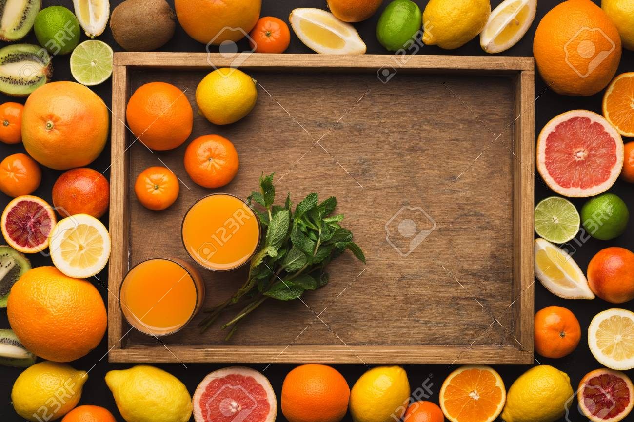 99922450 top view of citruses assortment and glasses of orange juice on wooden tray detox breakfast and healt