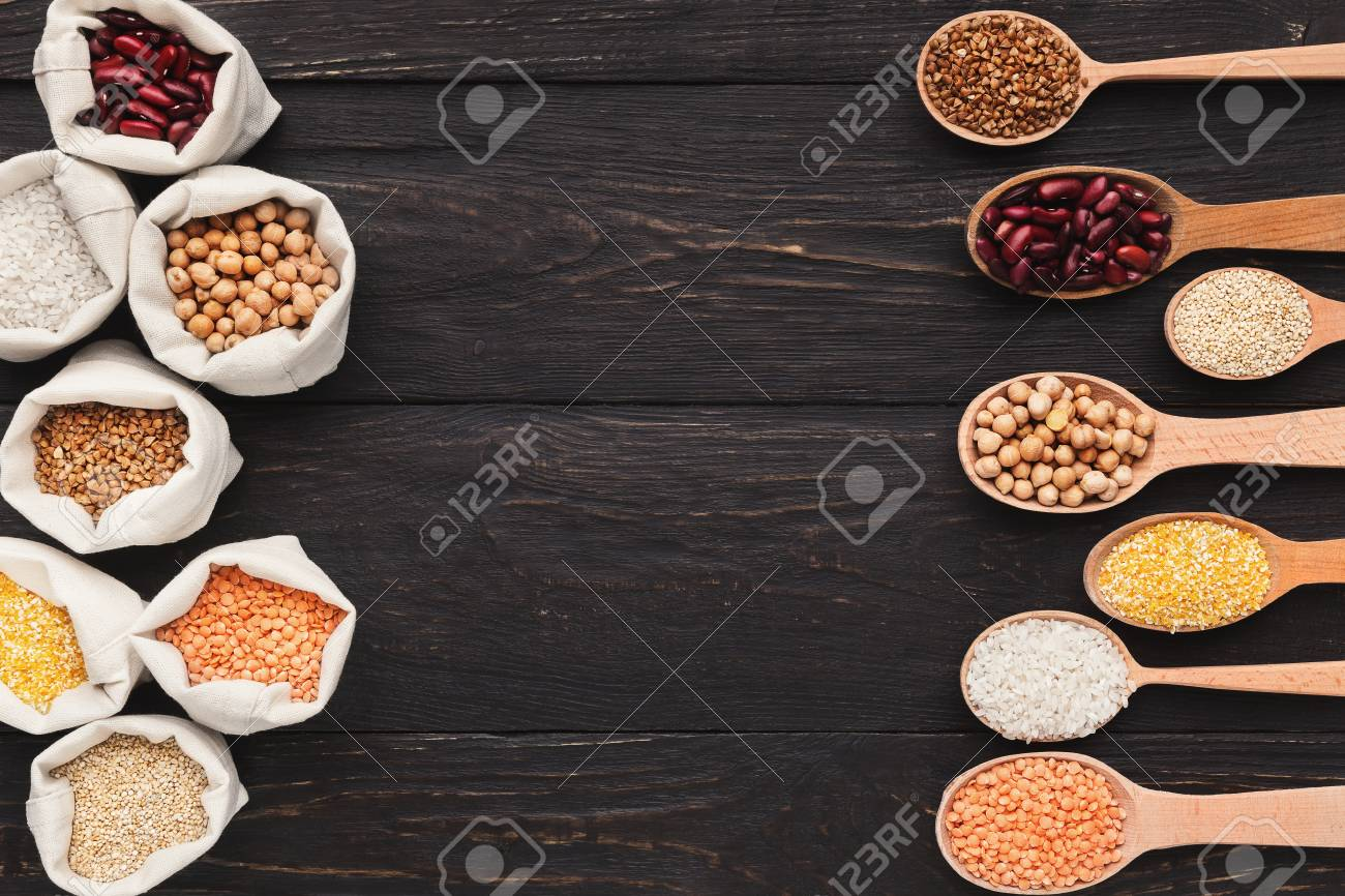 Various grains in cloth bags and spoons on wooden background, top view, copy space - 112543604