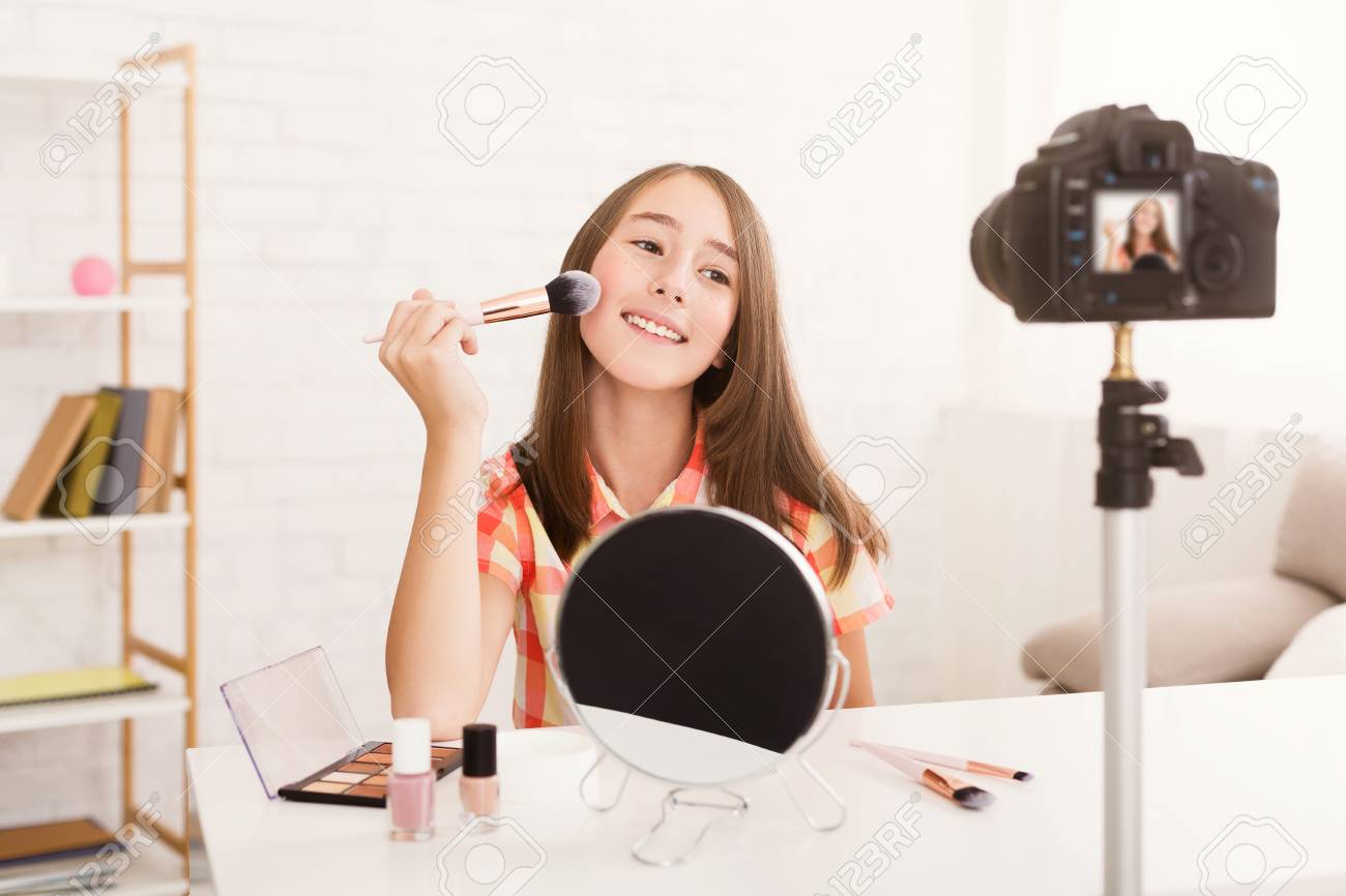 Charming pre-teen girl applying powder to her cheek and recording