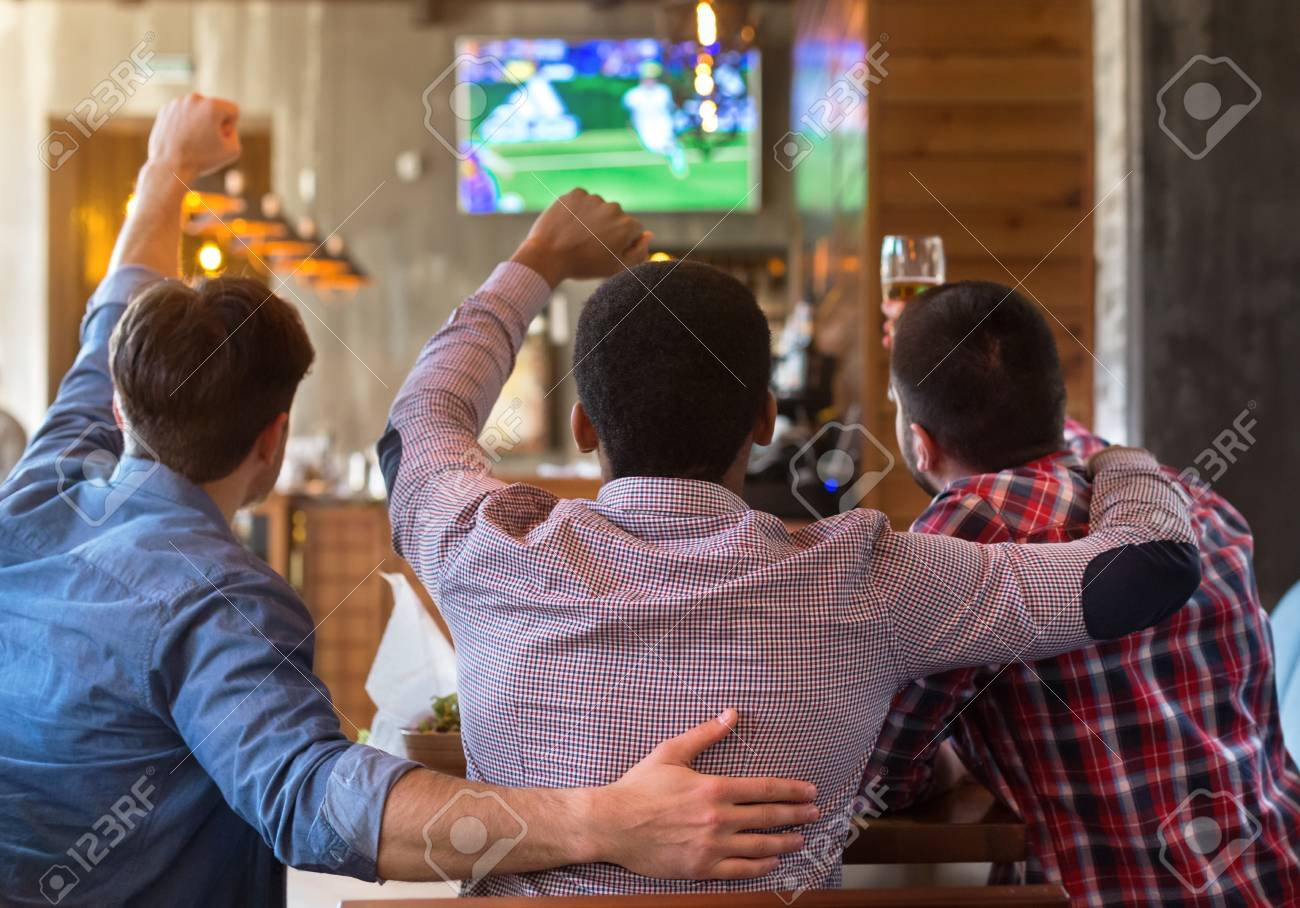 Male friends watching football match on TV in sport bar, back view - 119158927