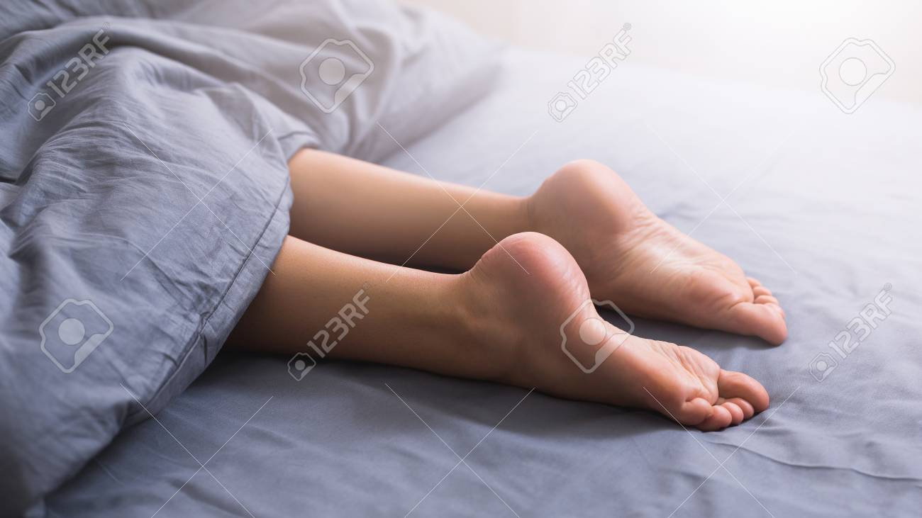 Beautiful female legs with smooth sole lying in bed under blanket, panorama, closeup - 115935577