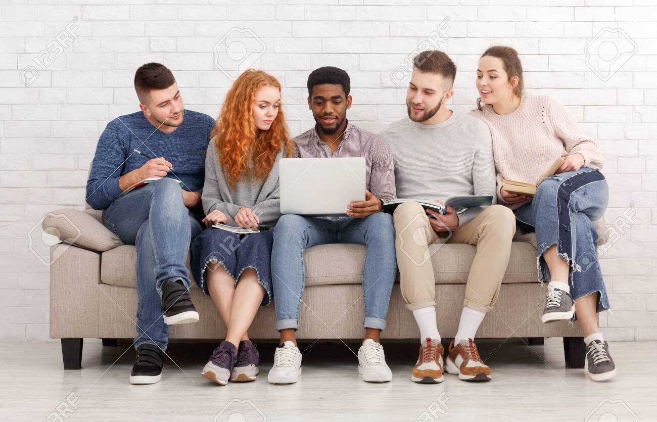 Students preparing for exams together, sitting on sofa over white wall - 120156486