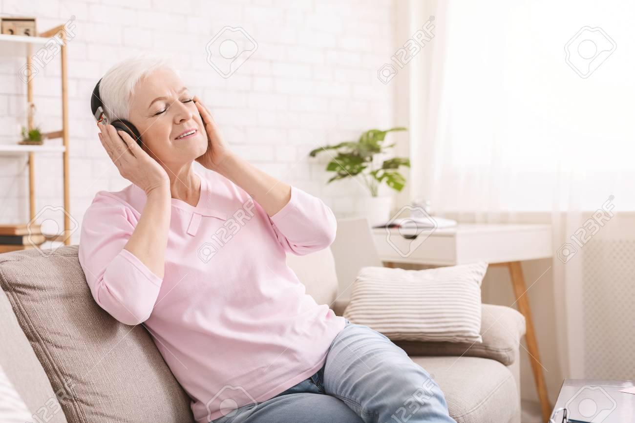 New life of favorite book. Senior woman enjoying audiobook in headphones, free space - 121034948