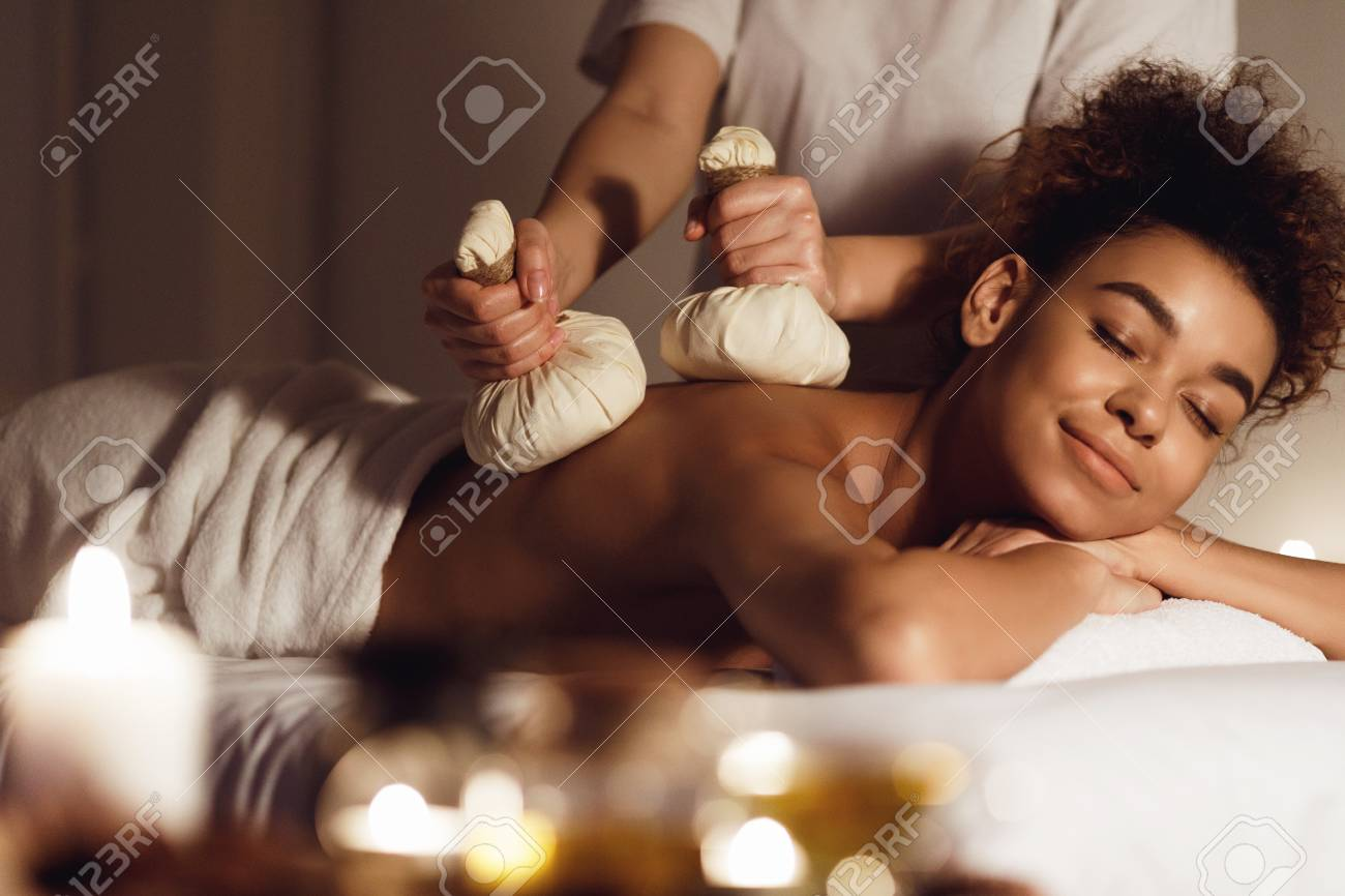 Thai herb compress massage. Woman relaxing in beauty spa, lying with closed eyes - 121038966