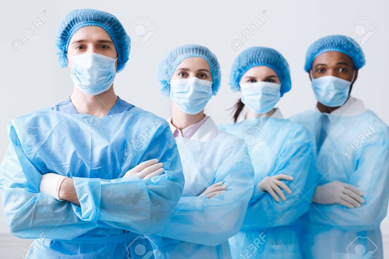Surgeons Team Ready for Surgery. Practitioners Wearing Protective Uniforms, Caps And Masks - 124593633