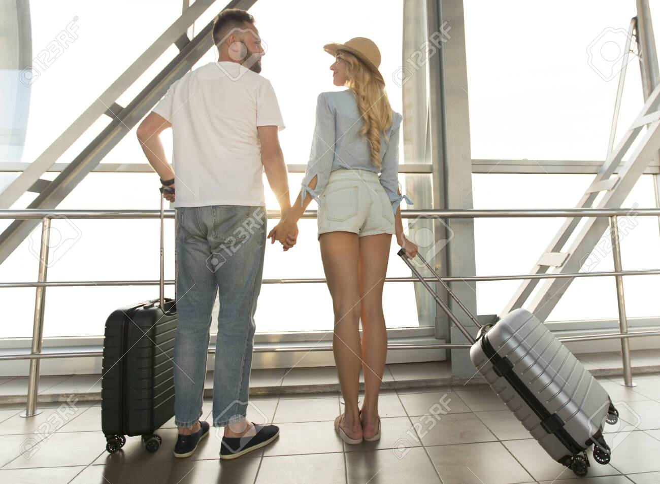 Traveling concept. Loving couple standing near window of international airport terminal, back view - 128090746