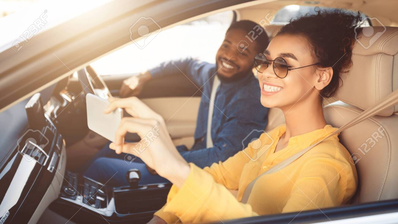Happy african american couple taking selfie in car, driving to new destination, free space - 128384812