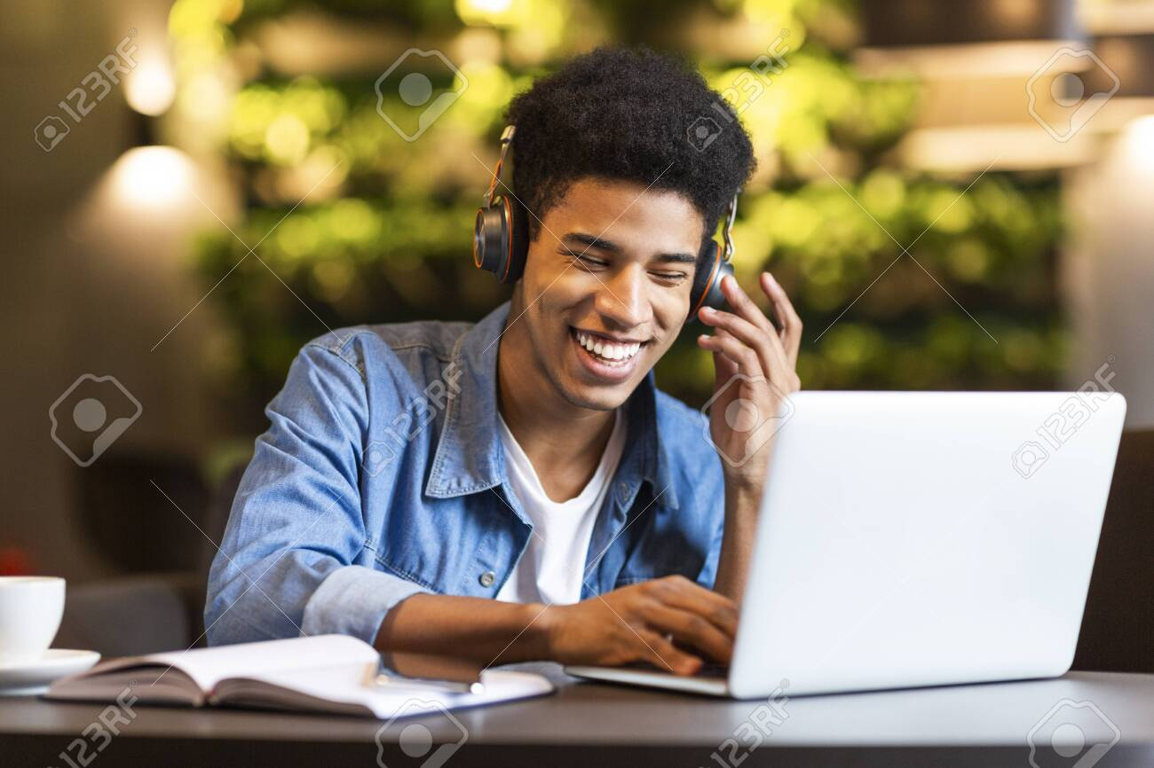 Cheerful black young guy with headset looking at laptop, having fun while studying, cafe interior - 129315453