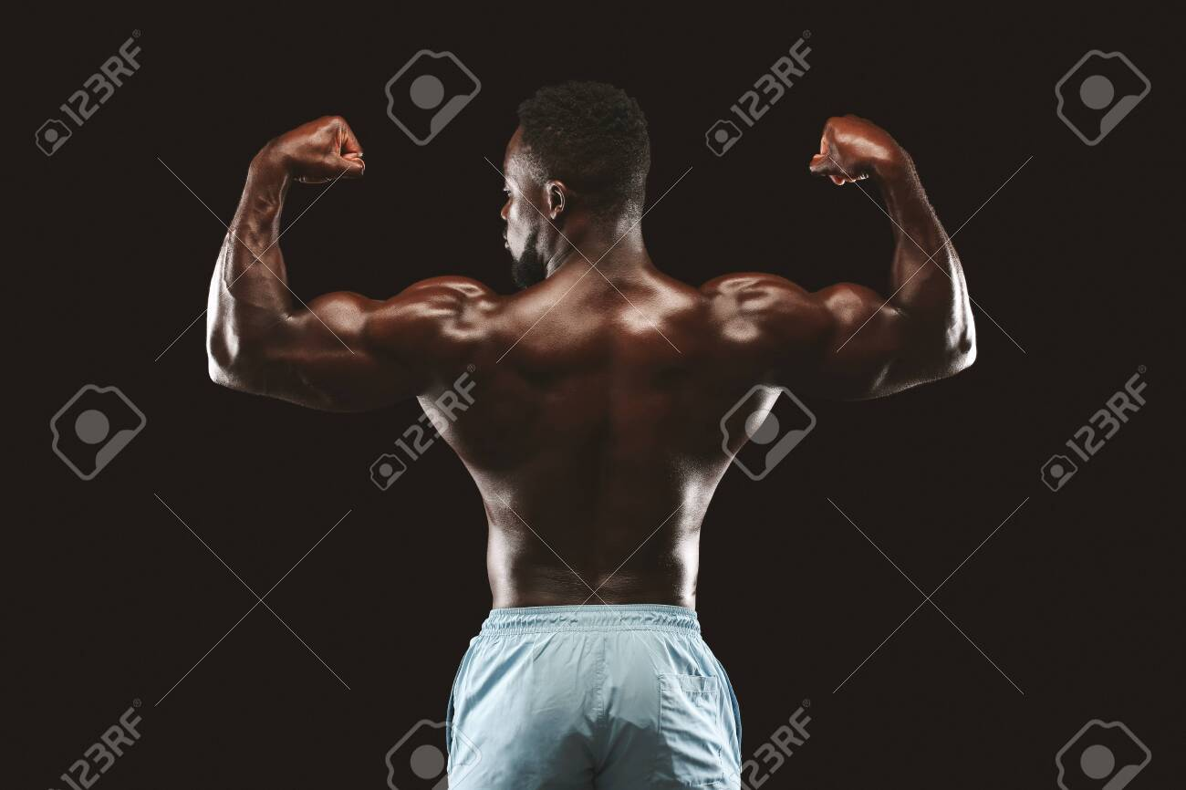 Muscular Athletic African Bodybuilder Fitness Model Posing After Exercises, back view over black studio background - 129610212