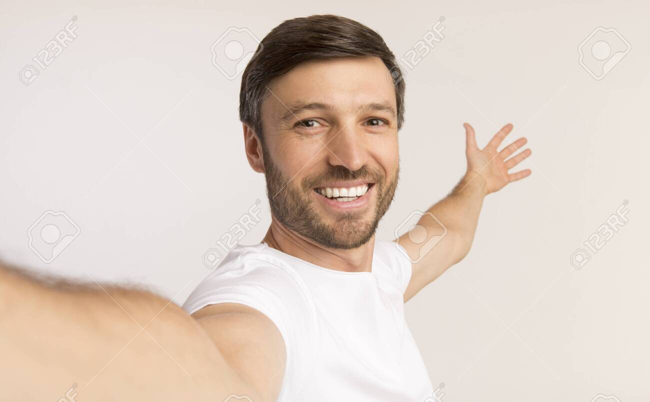 Look At This. Smiling Man Taking Selfie Gesturing With Hands Showing Something Behind Him On White Studio Background. Isolated - 129939464