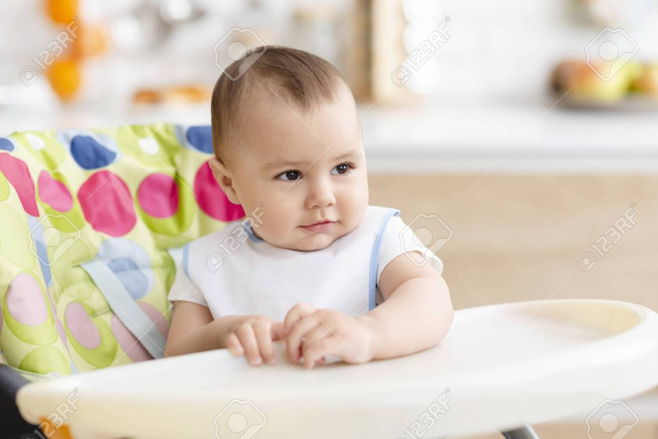 Dining time. Adorable baby sitting in high chair in kitchen , empty space - 130403698