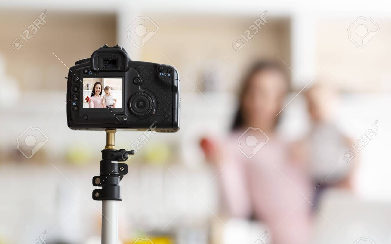 Baby nutrition online courses. Mother with toddler recording video for webinar, kitchen interior, empty space - 130628058