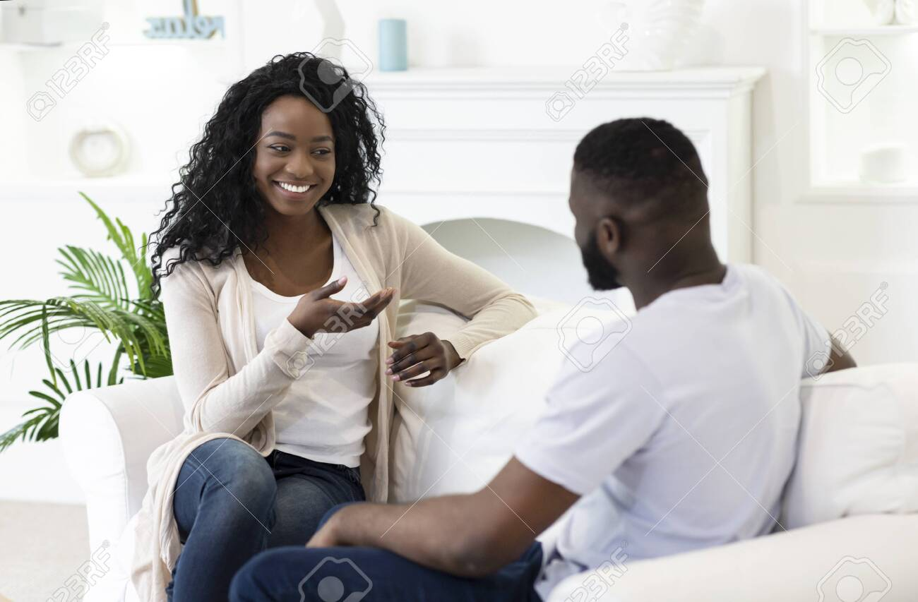 Pleasant conversation. Young husband and wife chatting together in living room at home. - 131947361