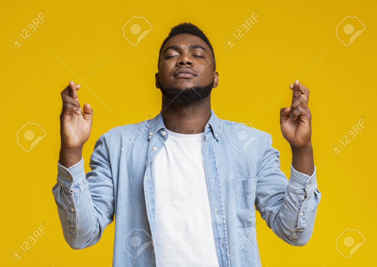 Cherished wish. Thoughtful african american man praying with crossed fingers and closed eyes, hoping for fortune and good luck - 132758884