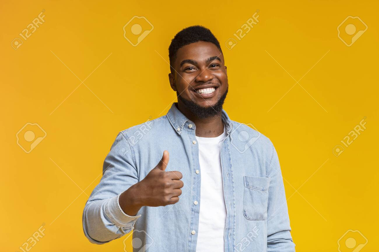 Right choice. Portrait of smiling blach guy showing thumb up at camera over yellow background with free space - 132853509