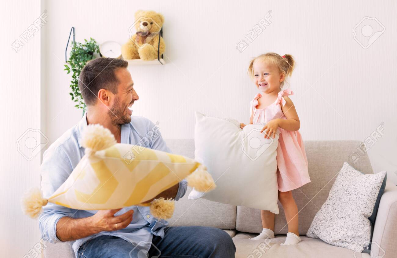 Family Morning Concept. Playful dad and daughter having a pillow fight together in the bedroom - 134341297