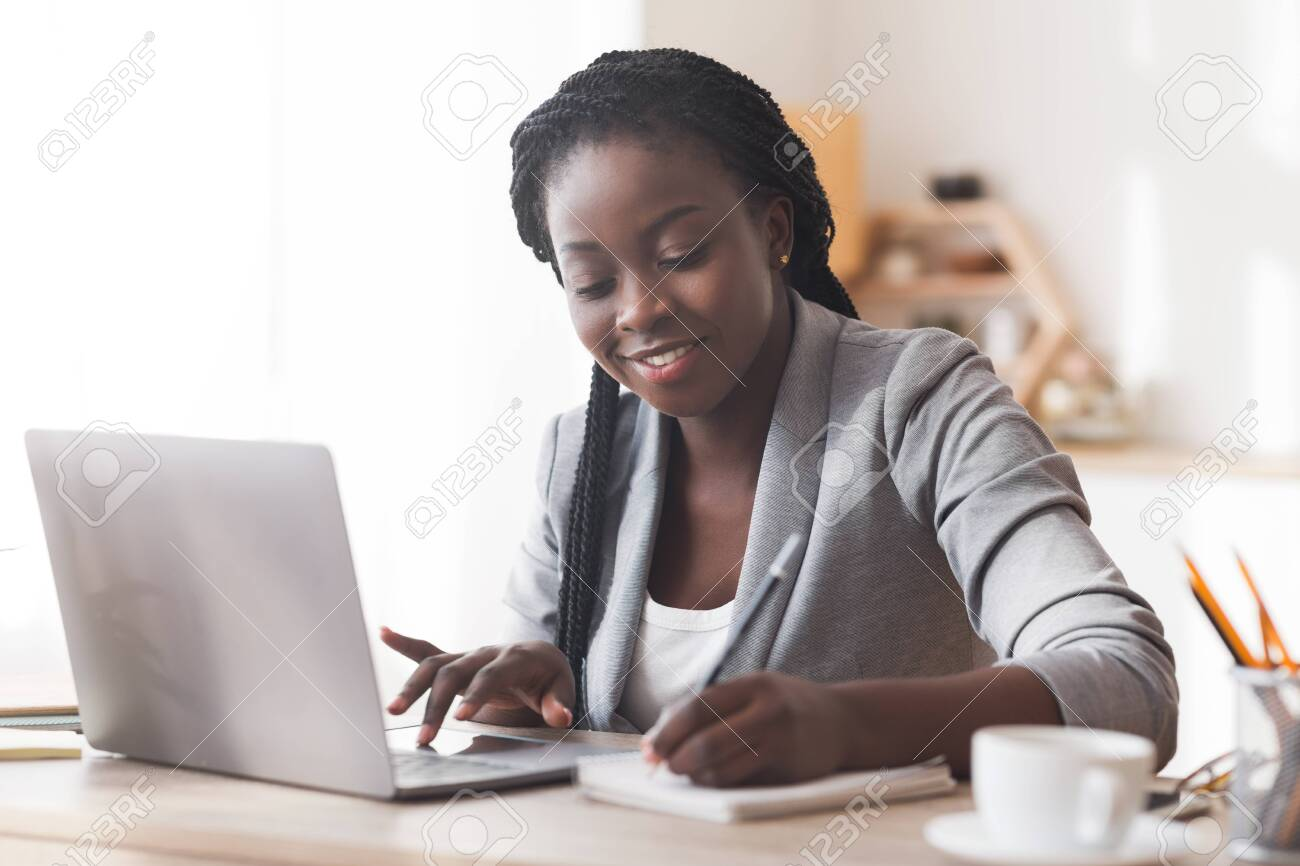 Black female entrepreneur working in office, typing on laptop computer and taking notes, free space - 134838294