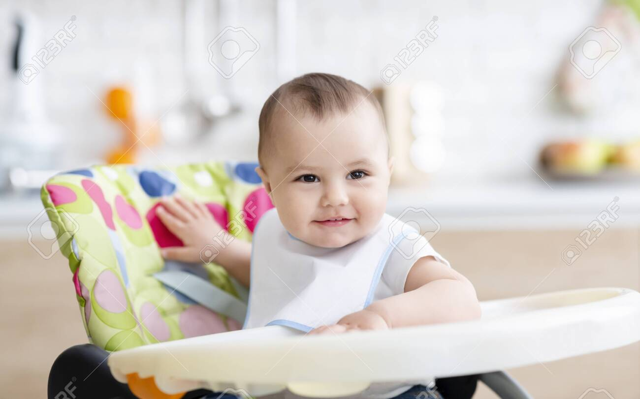 Happy baby boy smiling in high chair at kitchen - 139814905