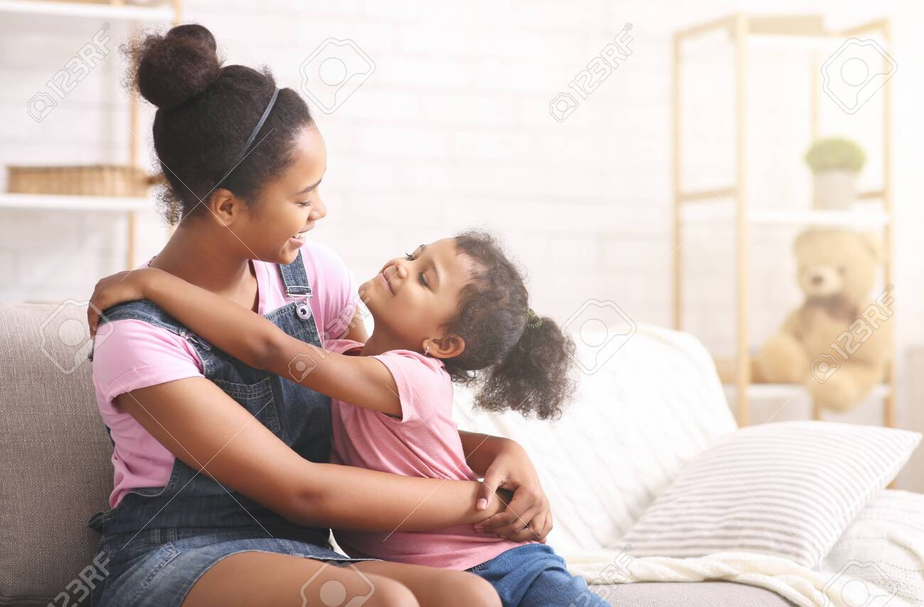 Family love. Cheerful african sisters hugging at home, empty space - 139834821