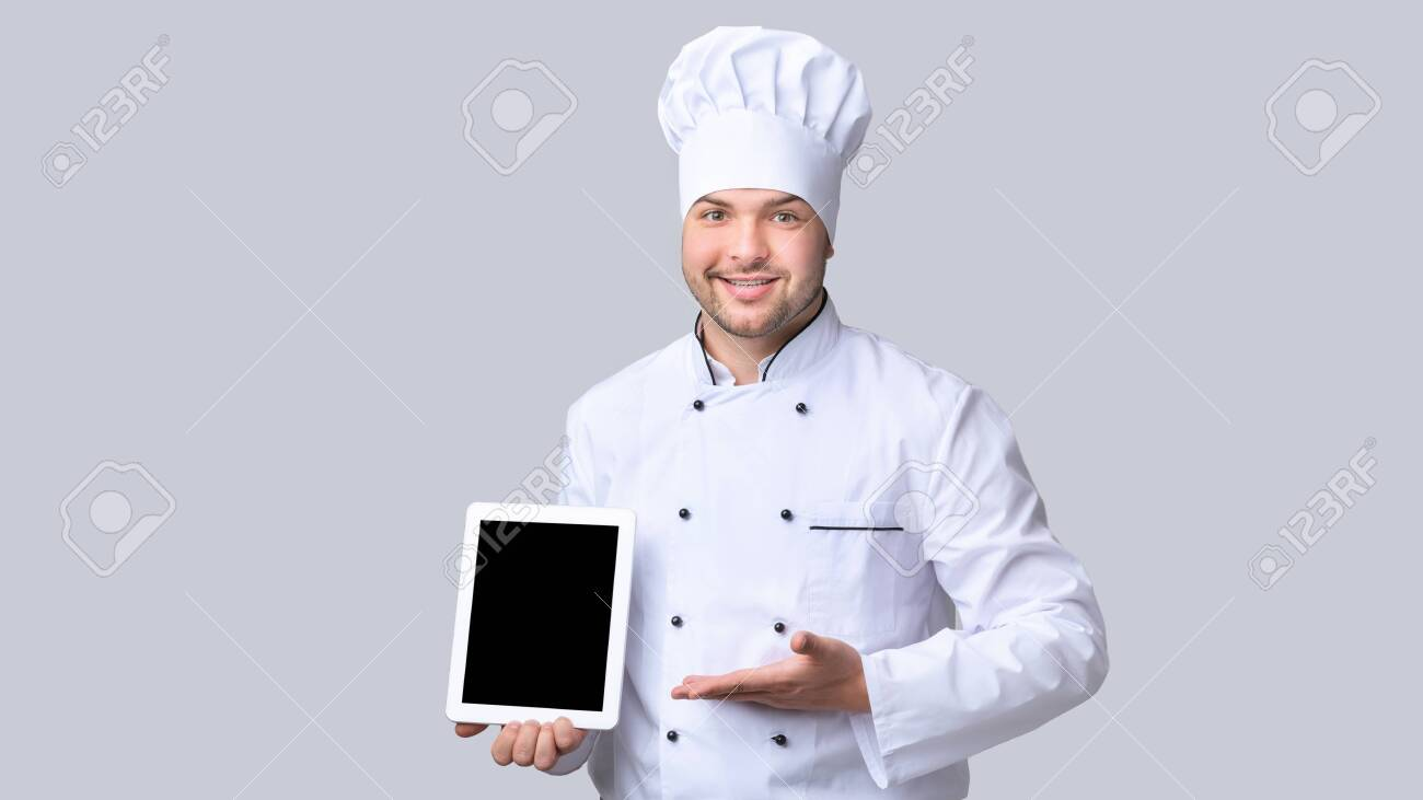Online Menu. Chef Man Holding Digital Tablet Showing Empty Screen Recommending Catering Service Standing On Gray Background. Mockup, Panorama - 140623529