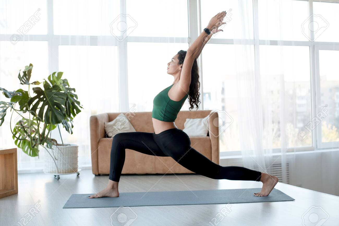 Healthy lifestyle and sports concept. Attractive Hispanic woman enjoying her morning yoga indoors. Warrior pose - 141060856