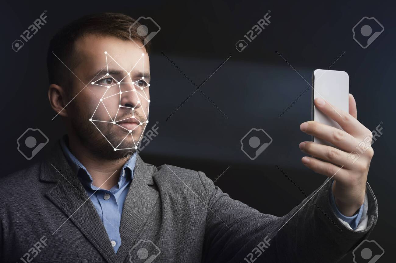 Unlocking smartphone with face recognition. Man with scanning mesh on face against black background - 142628162