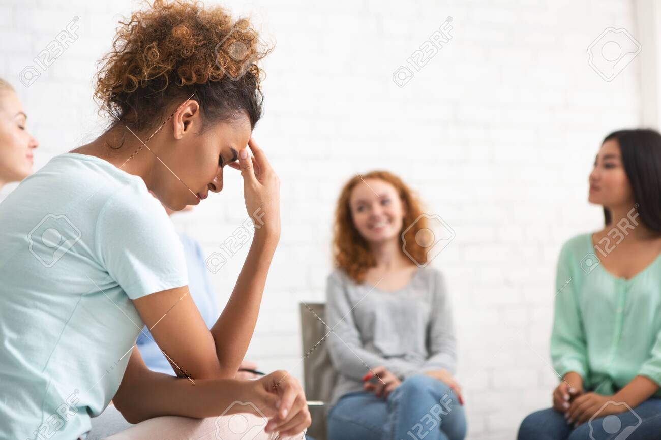 Depressed African Girl Sitting During Female Group Psychotherapy Session Indoors. Selective Focus - 143118202