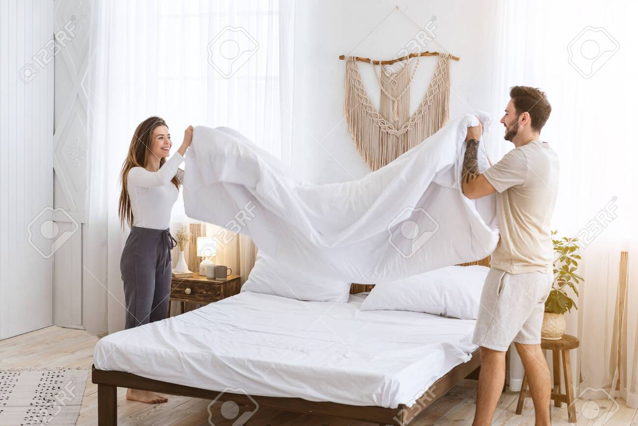 Couple Making A Bed Together Man And Woman Holding Blanket In Stock Photo Picture And Royalty Free Image Image 147085529