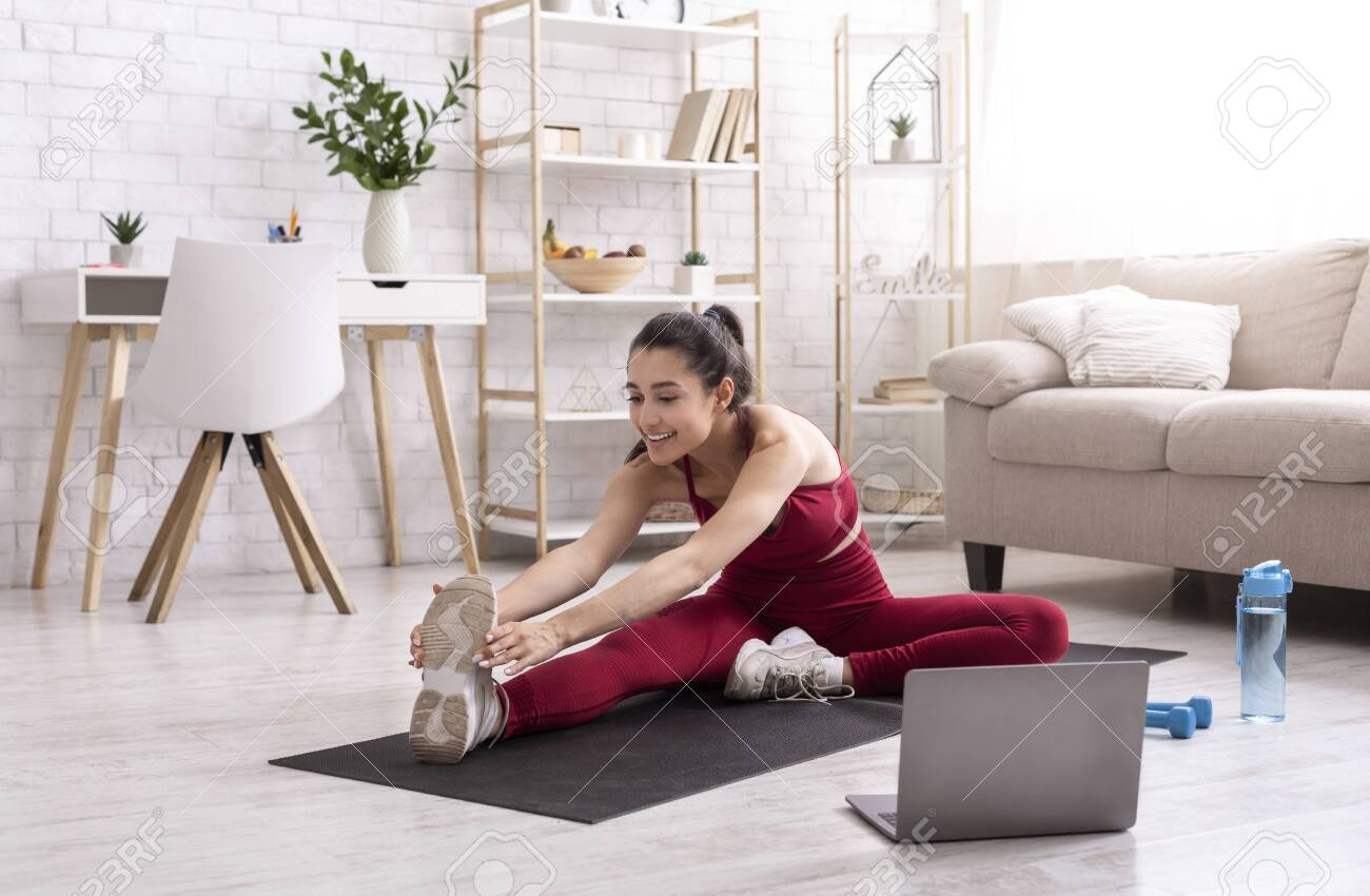 Female yoga instructor running online training session via laptop at home - 147720346
