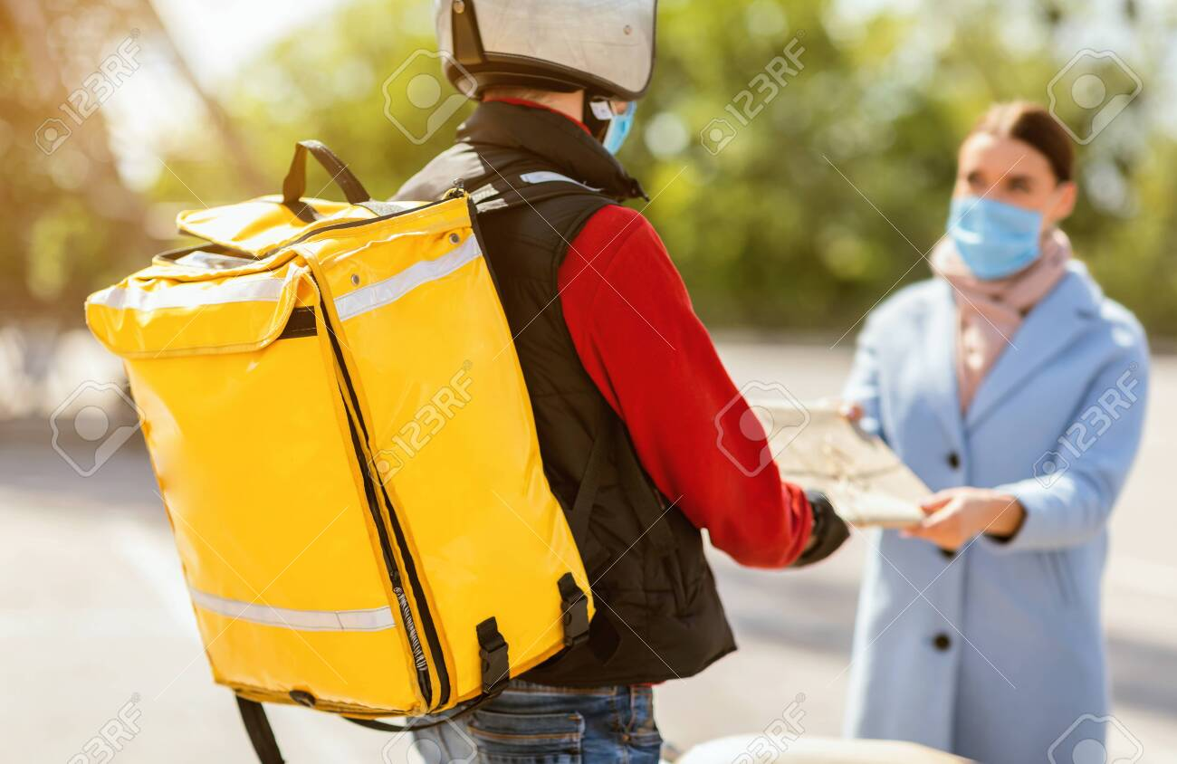 Fast Delivery. Courier Delivering Food Package To Woman Wearing Medical Mask Standing Outdoor In City. Cropped, Selective Focus - 148286657