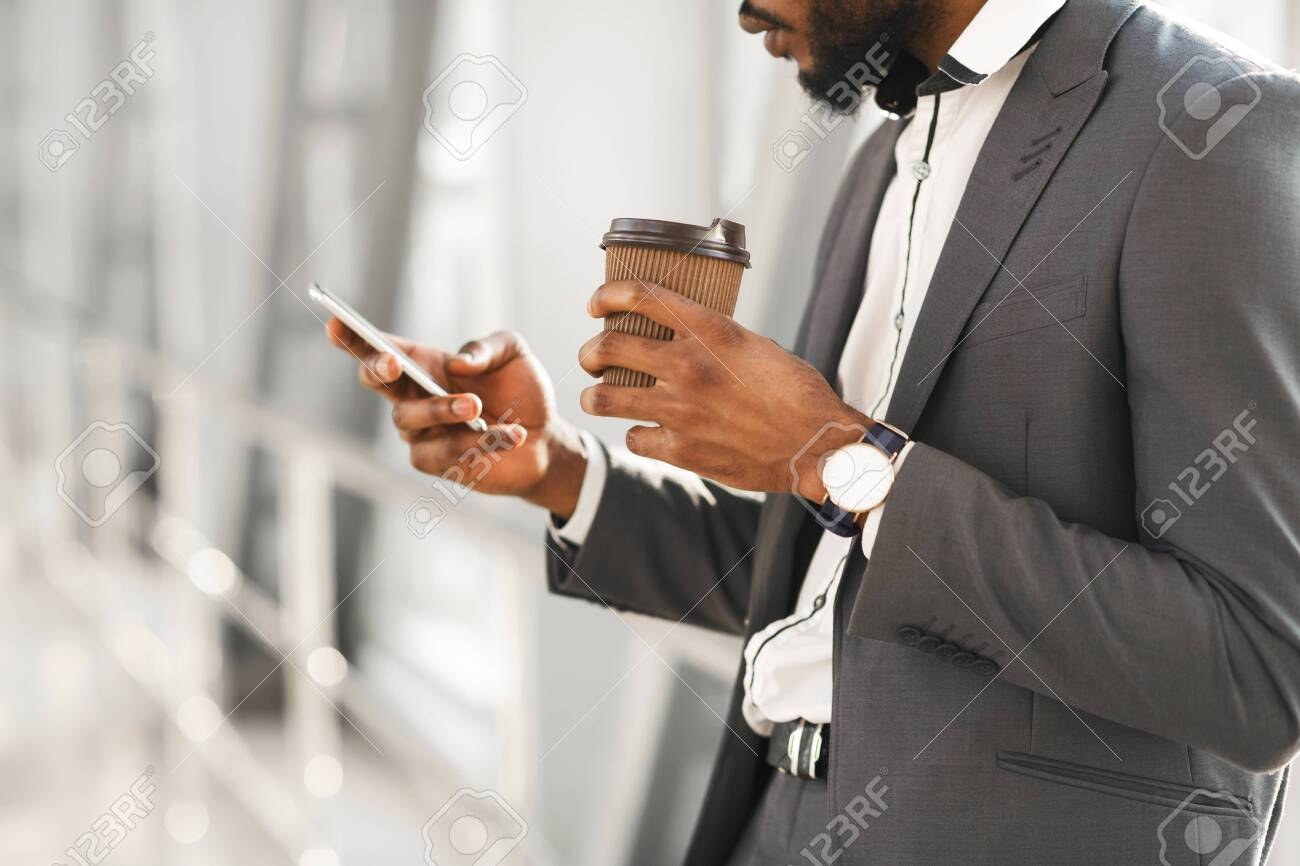 Waiting For Flight. Unrecognizable Black Businessman Using Smartphone Having Coffee Standing In Airport Indoors. Cropped, Selective Focus - 148367308