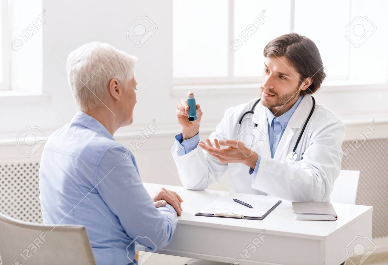 Doctor explaining pills schedule to senior patient during appointment at clinic - 149517332