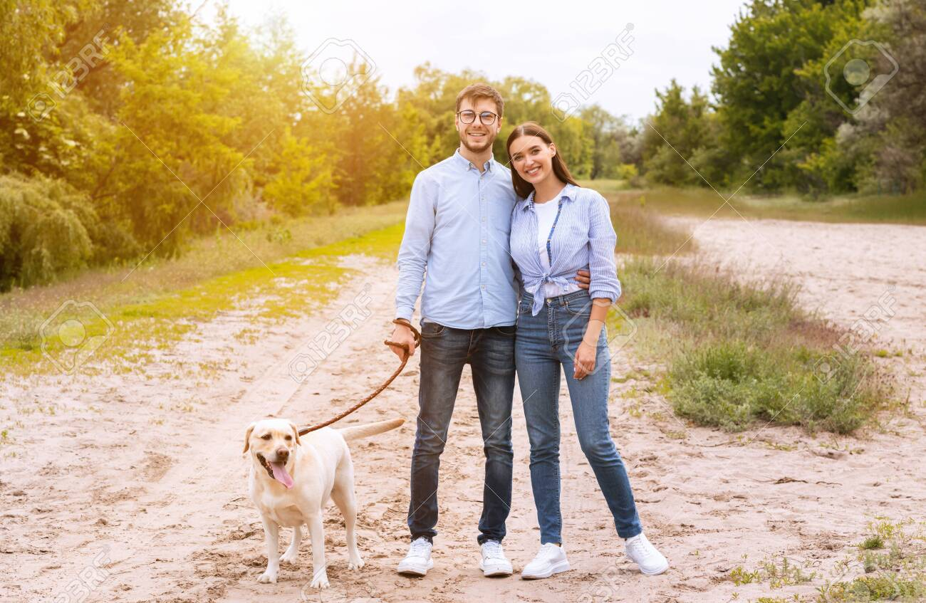 Family Portrait Concept. Casual boyfriend and girlfriend walking their labrador retriever in forest, posing at camera - 149873647