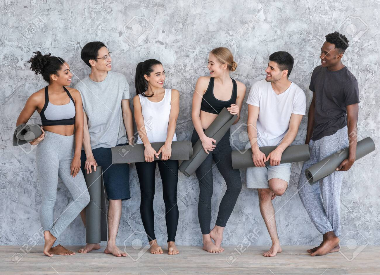 Healthy Lifestyle Concept. Group of sporty people with yoga mats resting after class near grey wall in fitness studio - 150632588