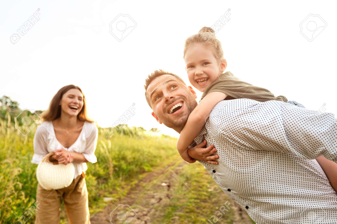 Fatherhood Concept. Portrait of excited dad piggybacking his daughter, resting in countryside on a sunny day - 154877042