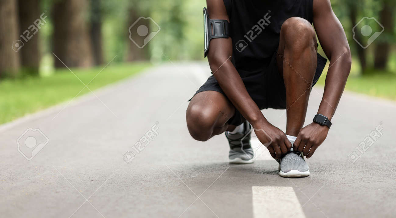 Unrecognizable african man tying his shoelaces on the street, jogging at park, panorama with copy space - 152021208